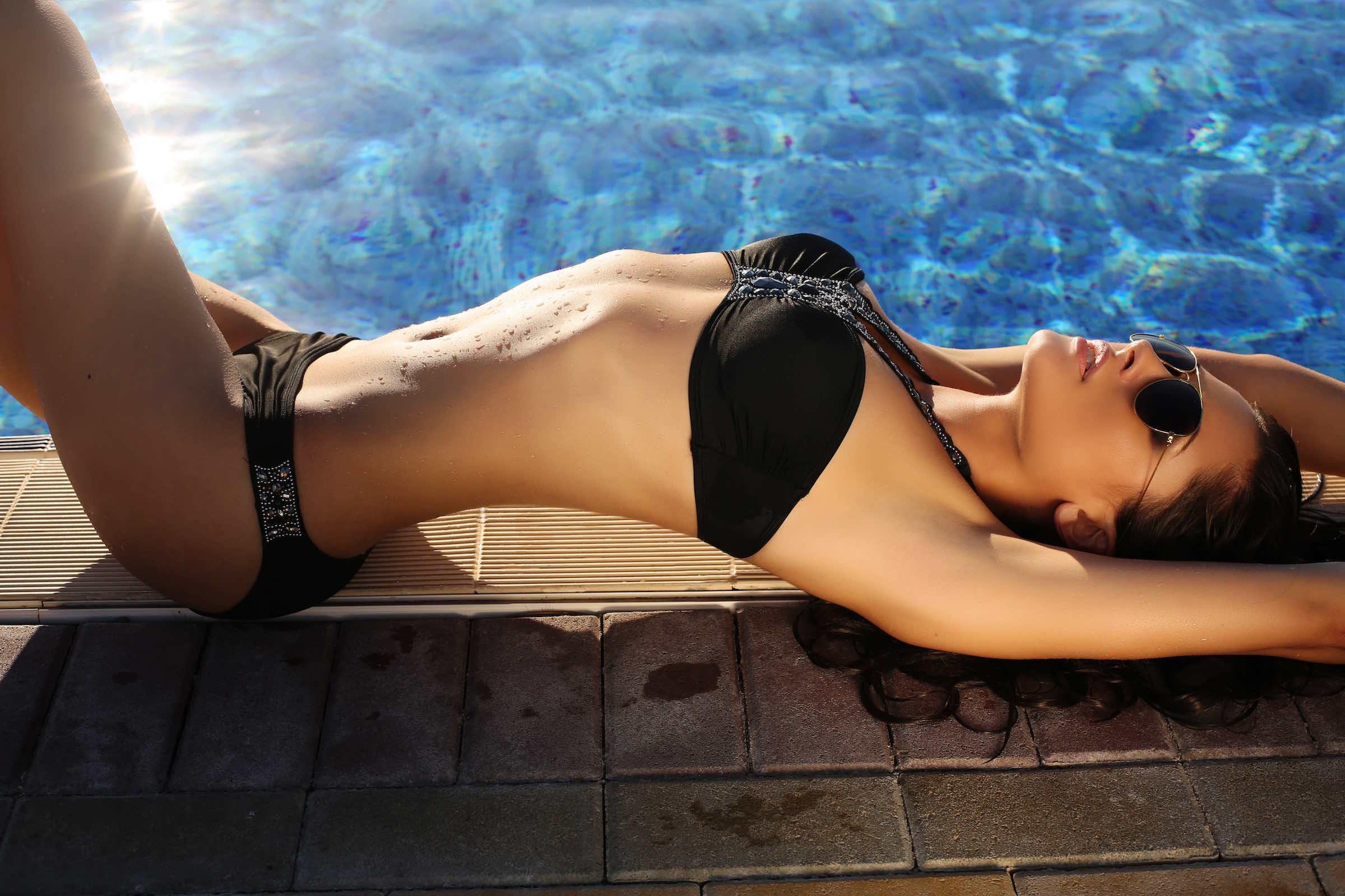 fashion photo of sexy beautiful girl with dark hair in black  bikini and sunglasses relaxing beside a swimming pool